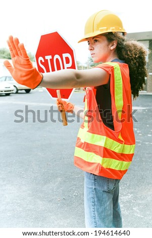Young female construction apprentice holding a stop sign and directing traffic.   - stock photo
