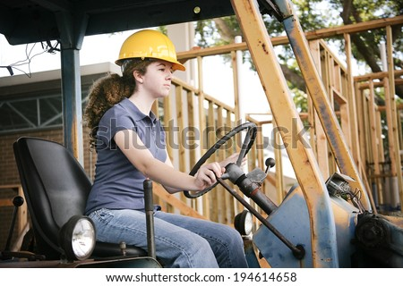Young female construction apprentice learning to drive heavy equipment.   - stock photo
