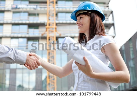 Young female construction engineer shaking hands at construction site - stock photo