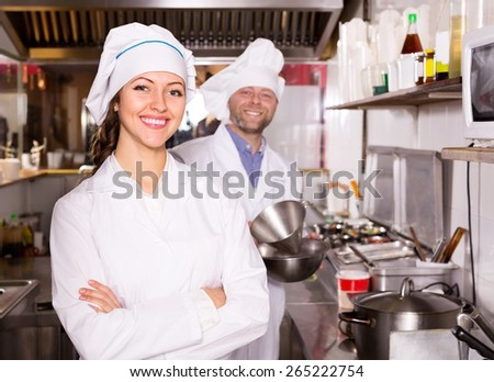 Young female cook cooking at professional kitchen in the take-away  restaurant - stock photo