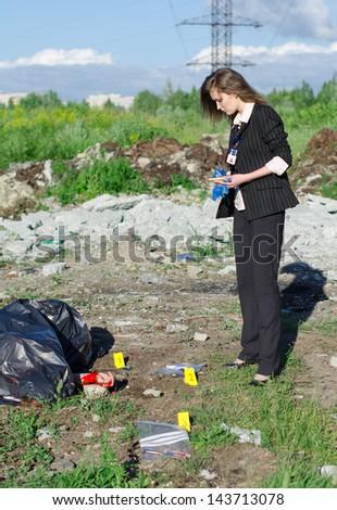 Young female criminalist inspecting crime scene - stock photo
