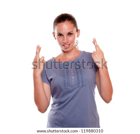 Young female crossing her fingers making a wish while is looking at you on blue blouse on isolated background - copyspace - stock photo
