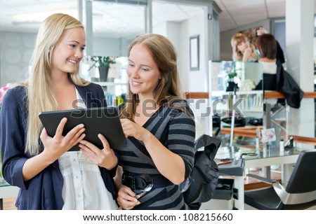 Young female customer holding digital tablet while standing with hairdresser at parlor
