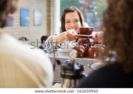 Young female customer taking coffee from barista in coffee shop - stock photo
