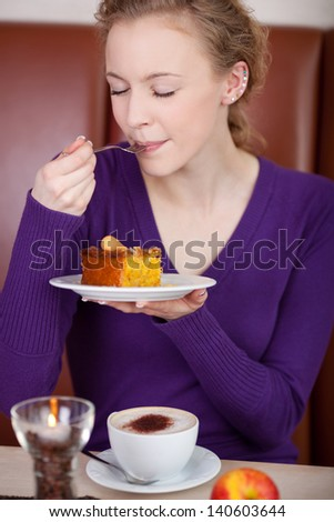 Young female customer with eyes closed enjoying pastry at coffee shop table - stock photo