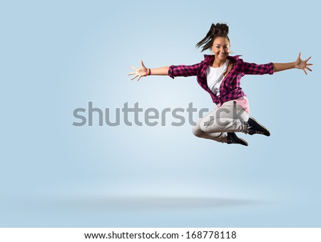 young female dancer, jumped up and opened her arms - stock photo