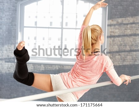 Young female dancer practicing by bar. View from back. - stock photo