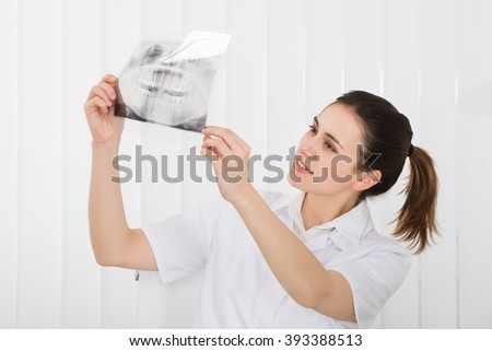 Young Female Dentist Looking At Dental X-ray In Clinic