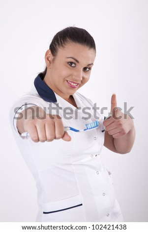 Young female dentist with toothbrush showing thumb up.