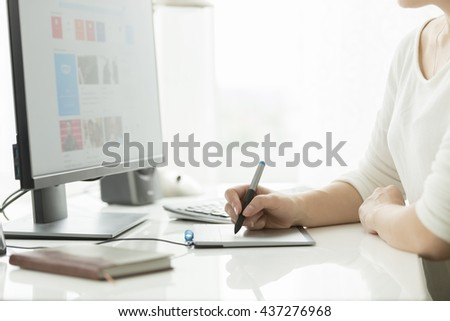 Young female designer using digital graphic tablet while working on computer - stock photo