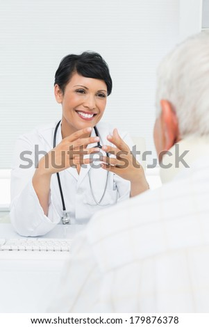 Young female doctor attentively listening to senior patient at the medical office - stock photo