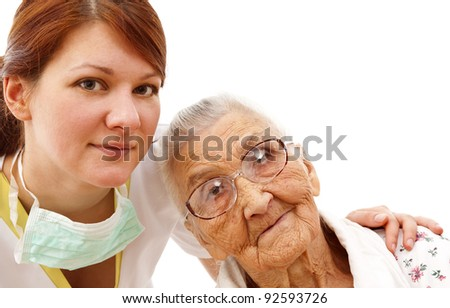 Young female doctor  caring about a very old female patient - stock photo