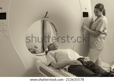 Young female doctor examining man in 40s with CT scanner. Computerised tomography. - stock photo