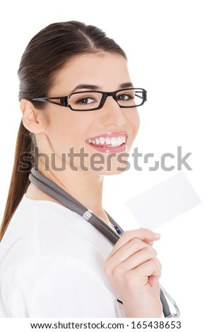 Young female doctor holding business card. Isolated on white.