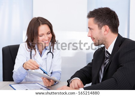 Young Female Doctor Holding Clipboard Talking With Businessman - stock photo
