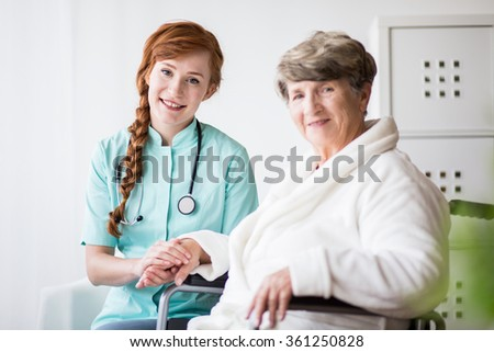 Young female doctor holding hand of senior woman - stock photo