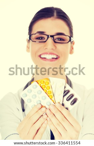 Young female doctor holding pills