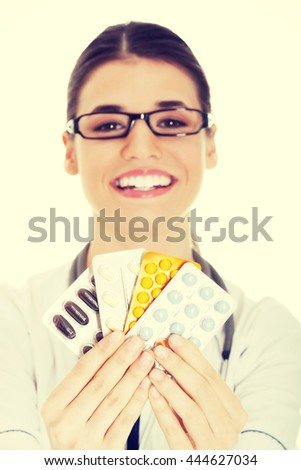 Young female doctor holding pills.