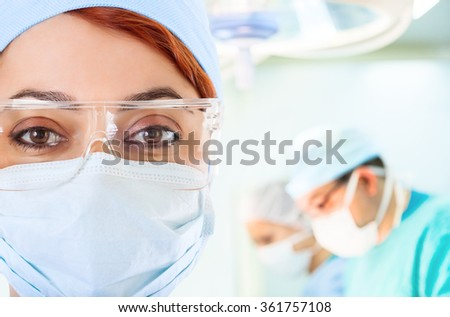 Young female doctor in operation room with her team on background  - stock photo