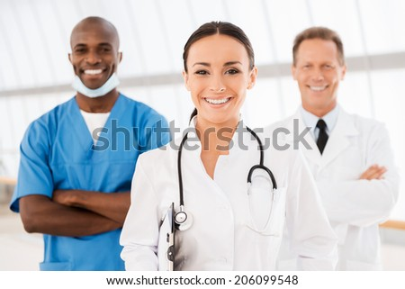 Young female doctor leading her team. Beautiful female doctor holding clipboard and smiling while her colleagues standing behind her in the background - stock photo