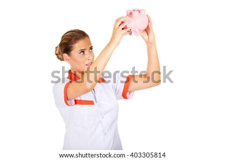 Young female doctor or nurse holding a piggybank - stock photo