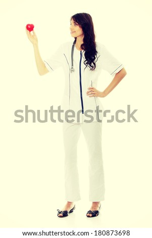 Young female doctor or nurse holding heart shaped toy - stock photo