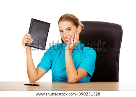 Young female doctor or nurse shows notebook - stock photo