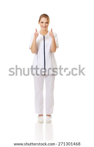 Young female doctor or nurse with thumbs up. - stock photo