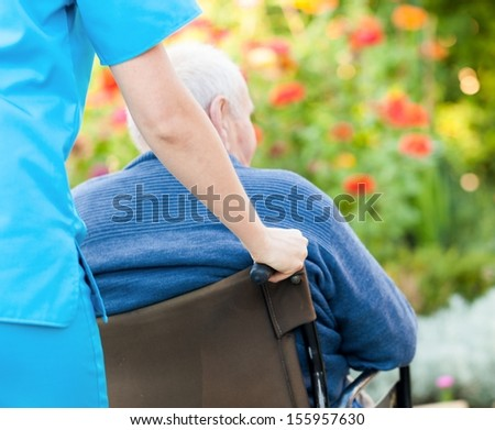 Young female doctor pushing and old patient in wheelchair. - stock photo