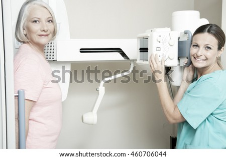 Young female doctor smiling during female patient medical scan.