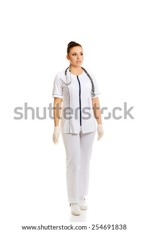 Young female doctor standing in uniform.  - stock photo