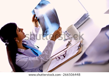 Young female doctor studying x-ray image, sitting at the desk - stock photo