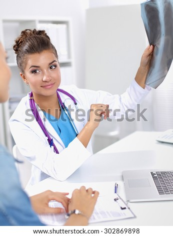 Young female doctor studying x-ray image sitting on the desk.