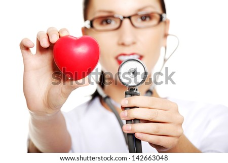 Young female doctor with heart in her hand. Isolated on white - stock photo