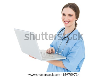 Young female doctor working with her notebook and smiling into the camera on white background