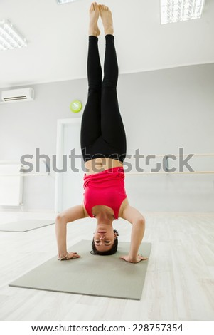 Young Female Doing Headstand Indoors - stock photo