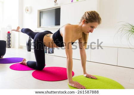 Young Female Doing Her Leg Raise Exercise In Living Room