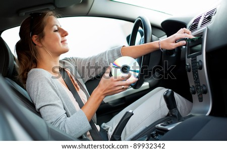 Young female driver playing music in the car (changing CDs) - stock photo