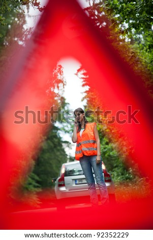 Young female driver wearing a high visibility vest, calling the roadside service/assistance after her car has broken down - stock photo