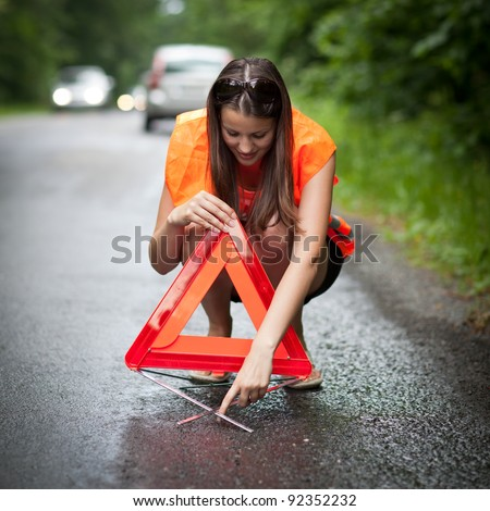 Young female driver wearing a high visibility vest, calling the roadside service/assistance after her car has broken down