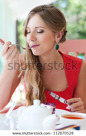 young female eating dessert with pleasure - stock photo