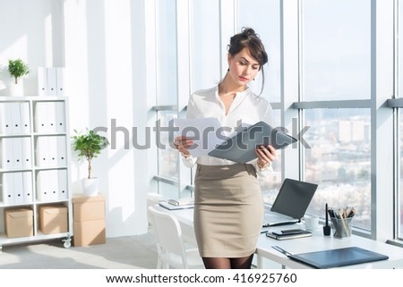 Young female employee, standing in office, wearing her work suit, reading business papers attentively, front view portrait. - stock photo