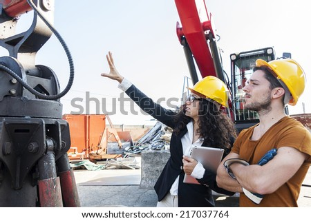 young female engineer talks about working with a worker - stock photo