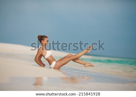 Young female enjoying sunny day on tropical beach of Maldives tropical island. Sexy sandy woman on tropical beach background near tropical Indian ocean - stock photo