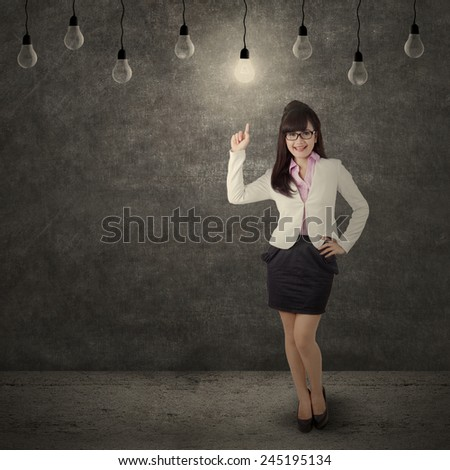 Young female entrepreneur get an idea and pointing at bright lightbulb - stock photo