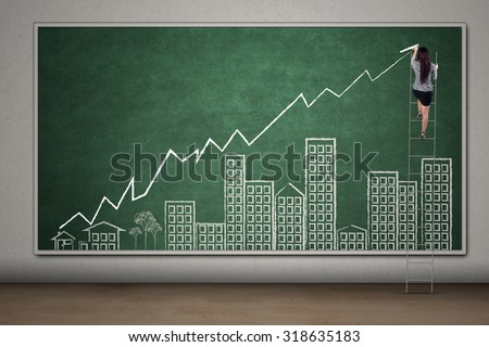 Young female entrepreneur using ladder to draw a real estate chart with arrow and building pictures on the chalkboard