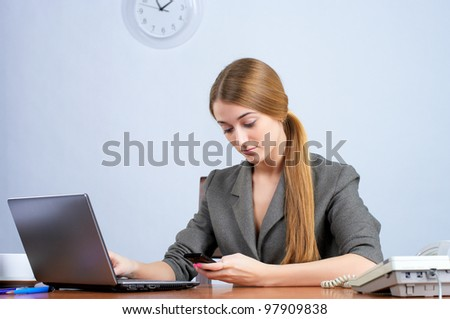 Young female executive at desk, calling cellphone - stock photo