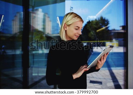 Young female executive director reading good news via digital tablet about company during work break outside, woman employee searching information on touch pad about client before meeting with him - stock photo