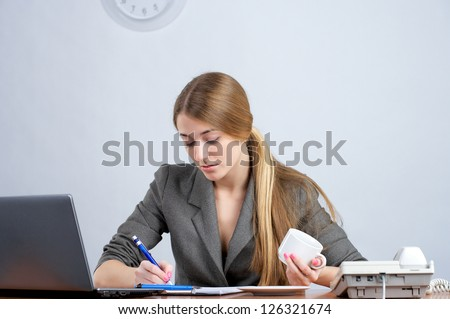 Young female executive writing in the document - stock photo