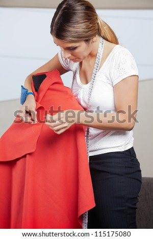 Young female fashion designer adjusting pins on a red fabric draped on mannequin - stock photo